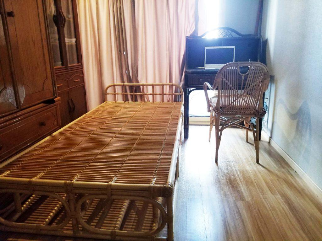 とても狭い部屋にベッドとデスクと書棚と籐椅子でめいっぱいです